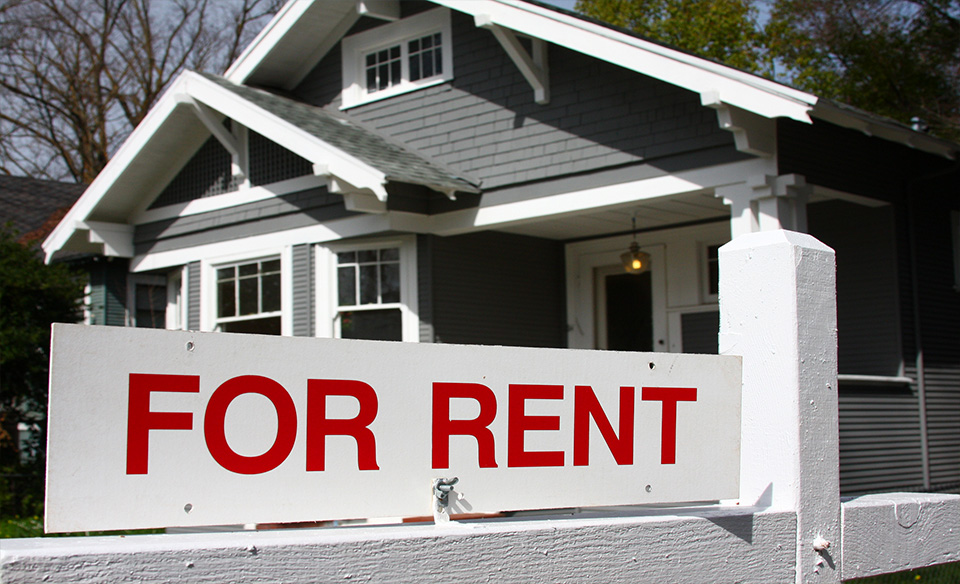 a home with a for rent sign in the front lawn